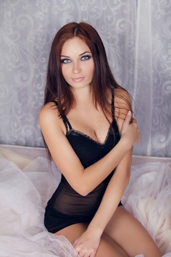 塑造美丽的深色的妇女画象在床上的 免版税库存图片