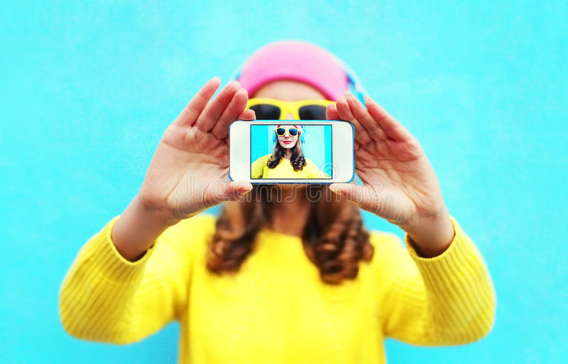 塑造采取在智能手机的凉快的女孩照片自画象在戴五颜六色的衣裳和太阳镜的白色背景 库存图片