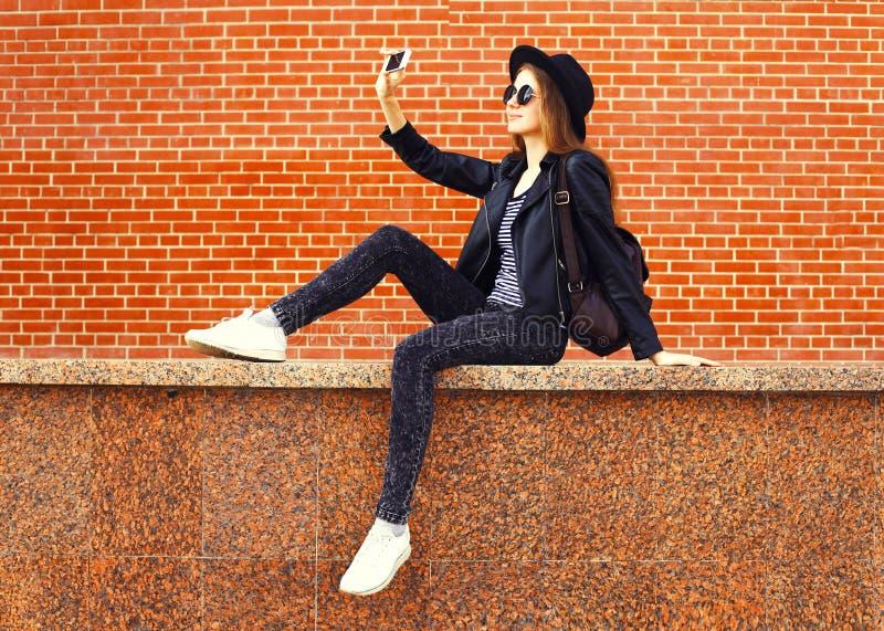 塑造采取照片在智能手机的俏丽的妇女图片自画象在岩石在砖背景的黑色样式 库存图片