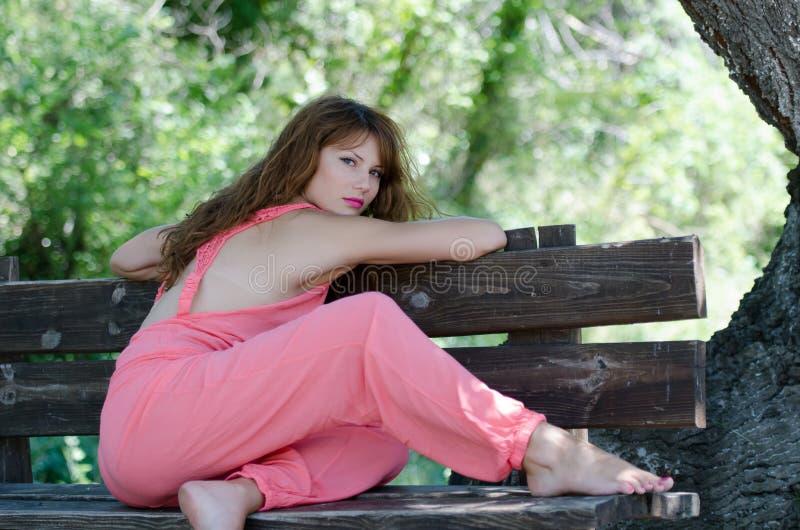 塑造长凳的妇女,与一套桃红色片断服装 库存图片