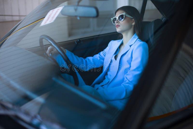 塑造驾驶在一套蓝色衣服的夫人一辆汽车 坐在汽车和拿着方向盘的时髦的女孩 免版税库存图片