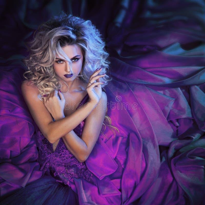 塑造年轻壮观的妇女照片蓬松紫色礼服的 工作室纵向 免版税库存照片
