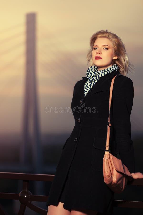 塑造黑外套的白肤金发的妇女有倾斜在篱芭的提包的 图库摄影