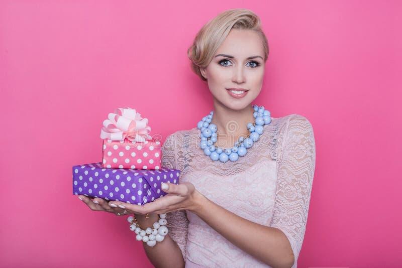 塑造年轻美丽的妇女射击有桃红色和紫色礼物盒的 库存照片