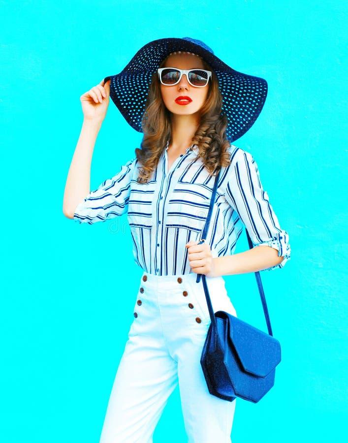 塑造画象佩带一台草帽、白色裤子和提包传动器在五颜六色的蓝色背景的少妇摆在城市 库存照片