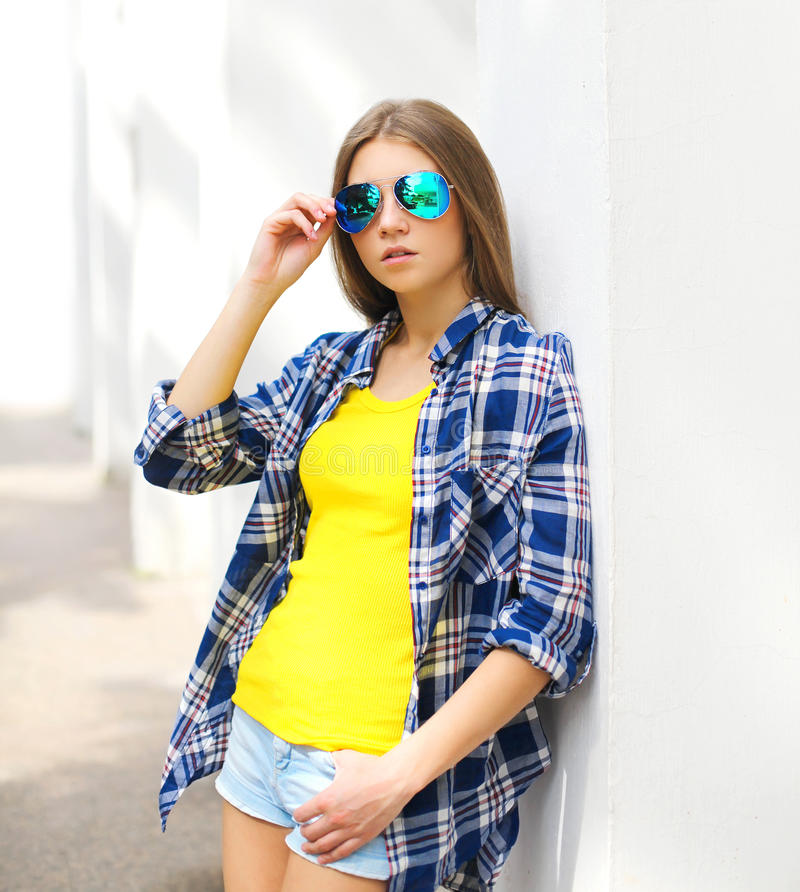 塑造画象女孩佩带太阳镜和方格的衬衣 库存照片