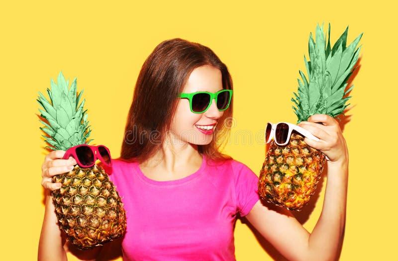 塑造画象微笑的妇女和两菠萝在太阳镜 免版税库存照片