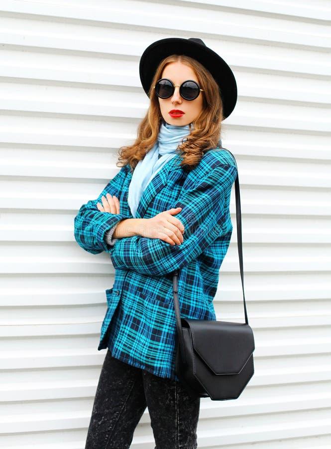 塑造画象相当少妇式样佩带的黑帽会议有提包的方格的外套夹克在白色 免版税库存照片