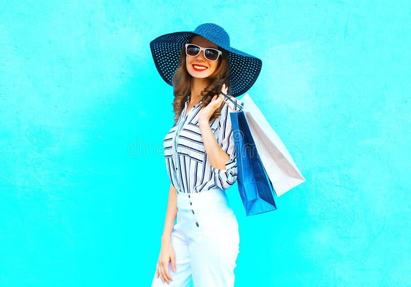 塑造画象年轻微笑的妇女佩带的购物袋,草帽,在摆在城市的五颜六色的蓝色背景的白色裤子 免版税库存照片
