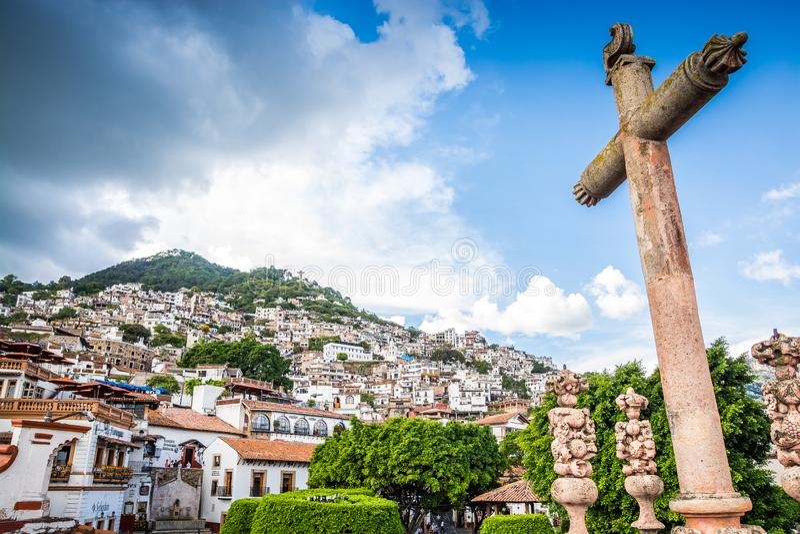 塔克斯科,墨西哥- 2018年10月29日 在大教堂和房子前面的十字架在墨西哥著名旅游城市 库存图片