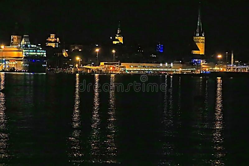 塔林、圣徒奥拉夫教会和巡航划线员在晚上,爱沙尼亚老镇的看法  免版税库存图片