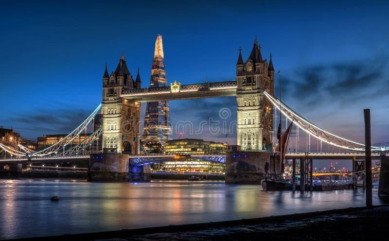 塔桥梁、碎片和伦敦地平线在黄昏 库存照片