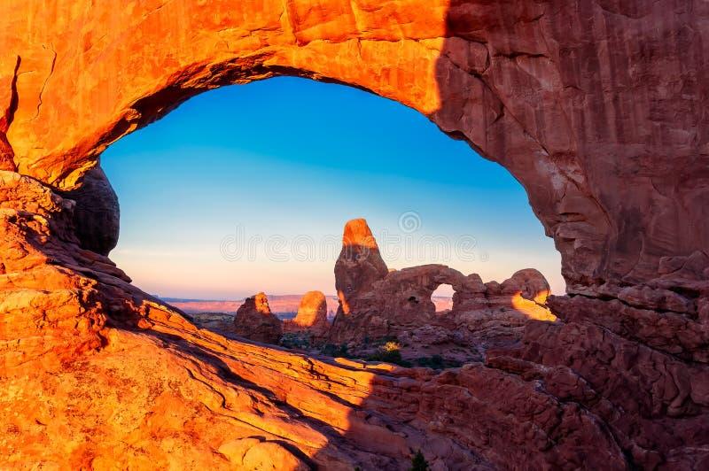 塔楼曲拱通过在日出的北部窗口在默阿布,犹他附近的拱门国家公园 图库摄影