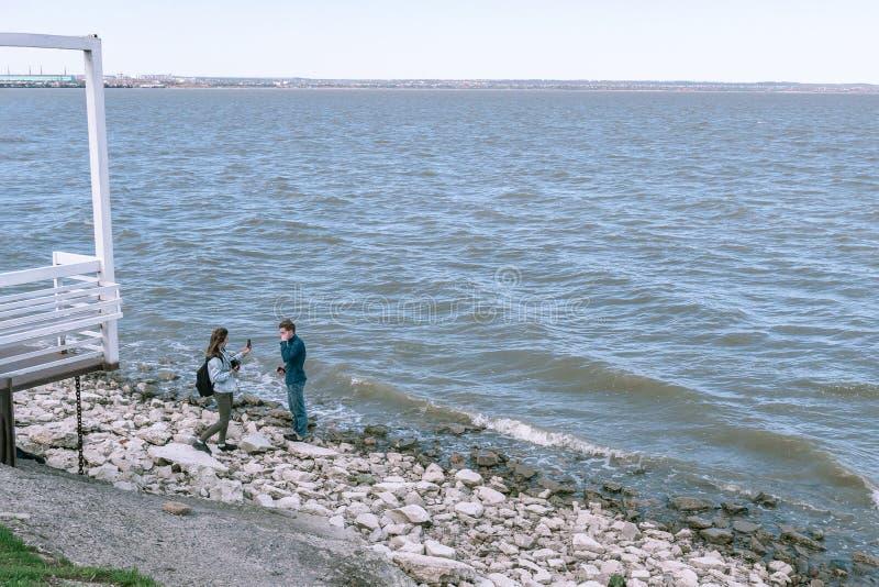 塔甘罗格,俄罗斯- 18 04 19:在电话的女孩照片她的在美丽的海附近的男朋友 免版税库存图片