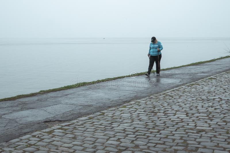 塔甘罗格,俄罗斯- 14 04 19:年轻女人向在多雨天气的体育求助 免版税图库摄影