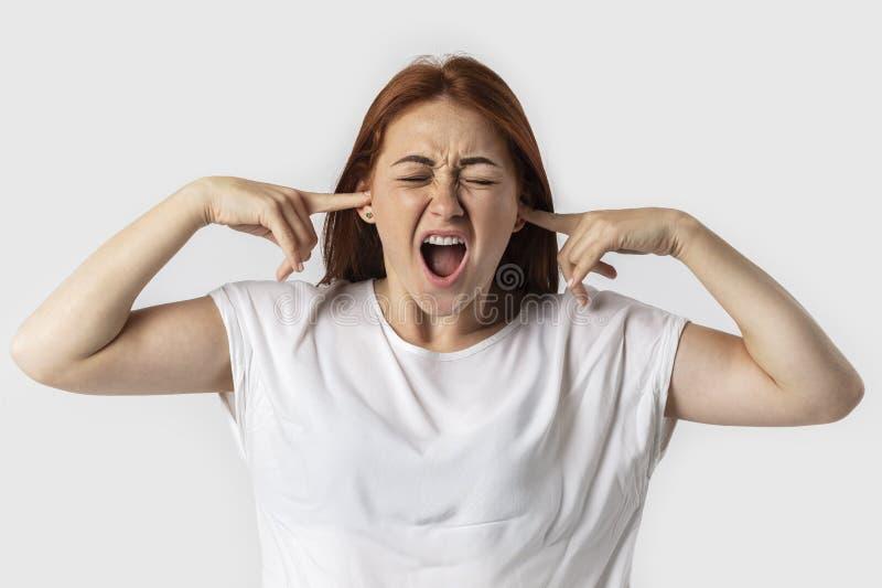 塞住她的有手指的耳朵和保持眼睛的Stressed沮丧的年轻红头发人女性闭上,当有头疼,不要能stan时 免版税库存照片