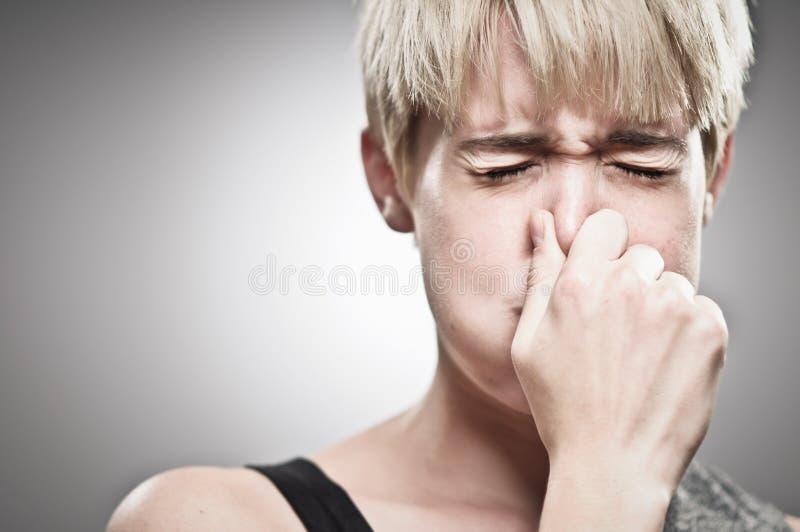 塞住她的鼻子的美丽的年轻白种人妇女 库存照片