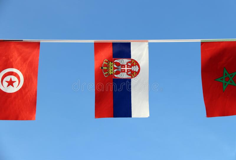 塞尔维亚,它的微型织品路轨旗子是三色的三条带红色蓝色和白色与中间偏左一点徽章的 库存图片