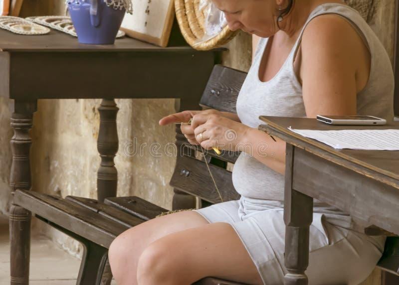 塞浦路斯,尼科西亚- 2019年6月10日:坐和运作在地方美术馆的妇女钩针编织织毛衣者的特写镜头手 库存图片