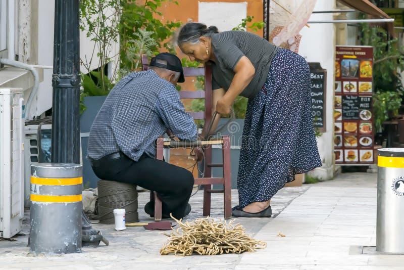 塞浦路斯,尼科西亚- 2019年6月10日:年长希腊夫妇做藤椅的男性和女性工匠在城市街道 ?? 免版税库存照片