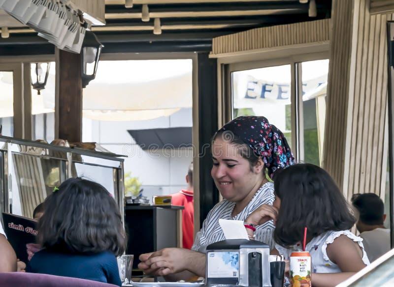 塞浦路斯,尼科西亚- 2019年6月10日:传统衣裳的年轻微笑的母亲在开放夏天享受与两个小女儿的一顿膳食 免版税图库摄影