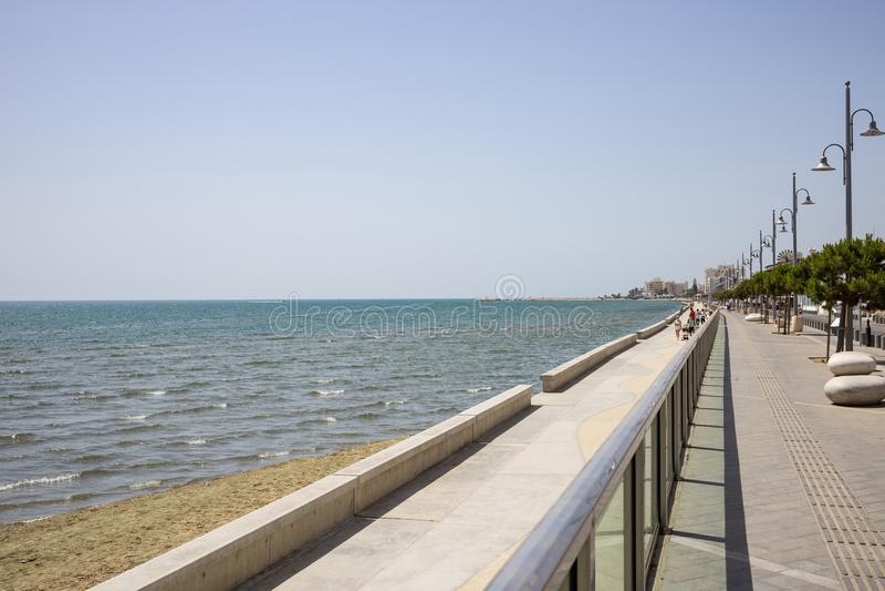 塞浦路斯,拉纳卡市 石道路在和在海上附近 口岸,海滩,大厦,蓝天背景 免版税库存照片