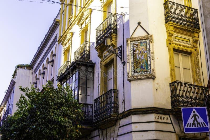 塞维利亚、西班牙- 2019年1月11日-壁角房子和在的壁画装饰的门面有扭转的wrought-iron阳台的 库存图片