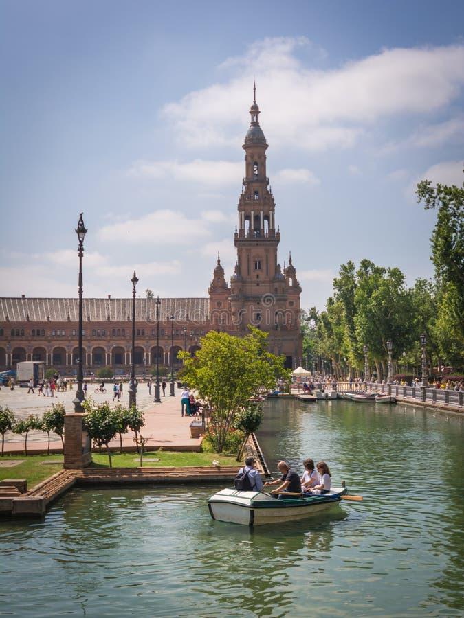 塞维利亚,西班牙- 2018年5月:游人在运河西班牙Square Plaza de西班牙,西班牙的一条小船2018年5月22日漂浮 免版税图库摄影