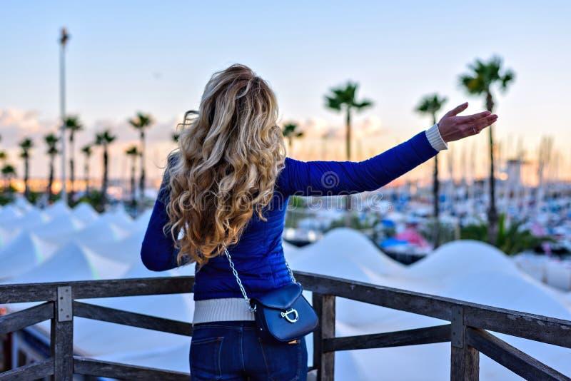 巴塞罗那口岸的女孩在日落 葡萄酒获得年轻时髦的白肤金发的妇女城市画象乐趣,单独移动 库存照片