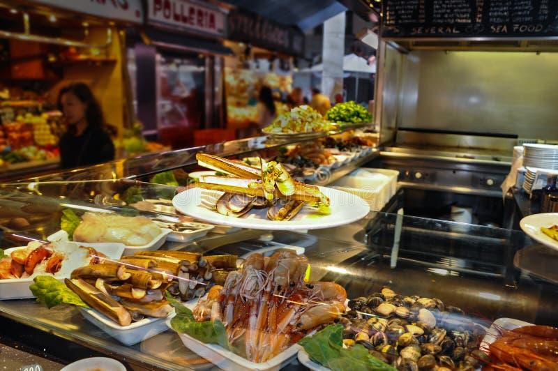 巴塞罗那西班牙- 2016年5月:虾,竹起重器刀子蛤蜊和淡菜在冰在咖啡馆玻璃容器在梅卡de Boqueria市场上 免版税库存图片