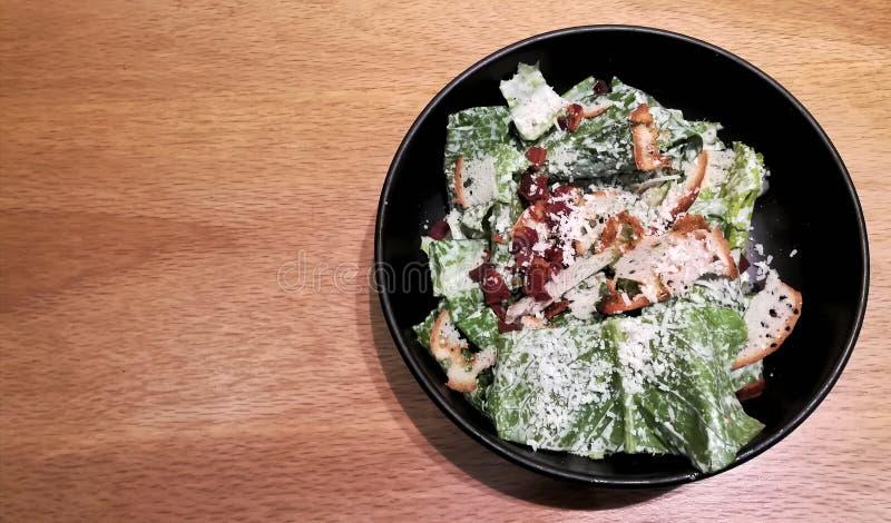塞萨尔省沙拉用绿色菜乳酪和酥脆烟肉在一个黑碗在木桌上 免版税库存照片