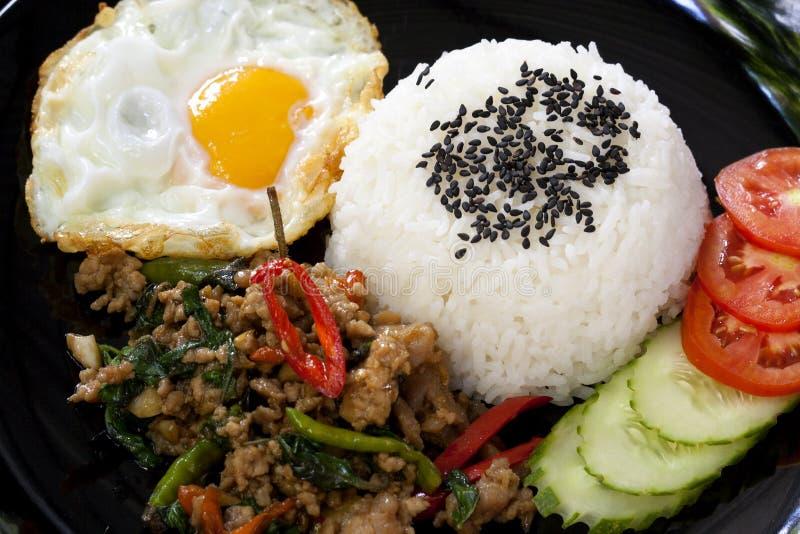 填塞与蓬蒿的KRA PAO、泰国辣油煎的猪肉和晴朗的煎蛋 免版税图库摄影