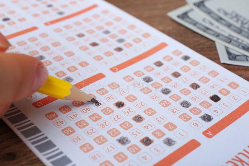 填好彩票的妇女用在桌,特写镜头上的铅笔 r 库存照片