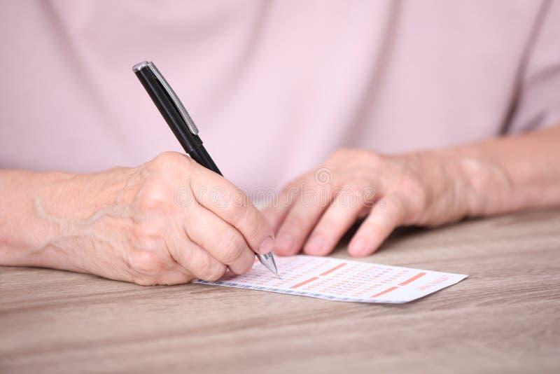填好彩票的资深妇女在桌上 图库摄影