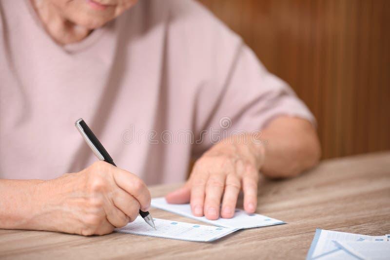 填好彩票的资深妇女在桌上 免版税库存照片