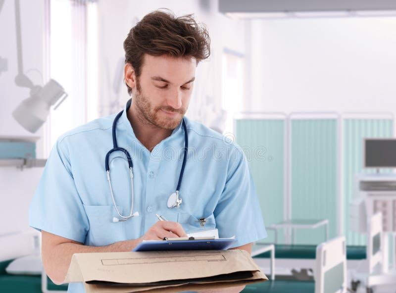 填好患者纪录的医生在医院 免版税库存图片