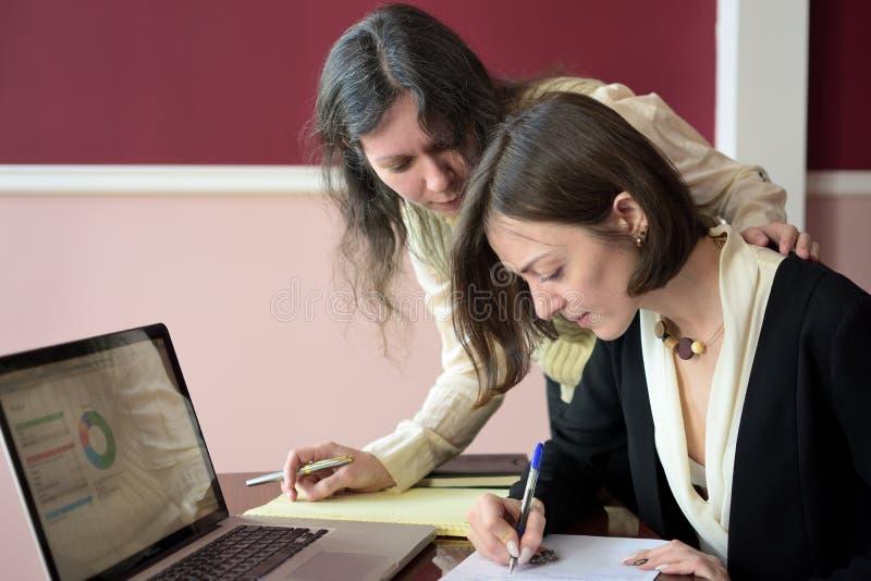 填好表格的两名年轻聪明地加工好的妇女在膝上型计算机前面的葡萄酒办公桌 免版税库存图片