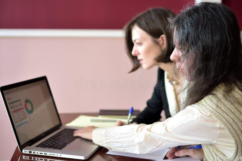 填好表格的两名年轻聪明地加工好的妇女在膝上型计算机前面的葡萄酒办公桌 免版税图库摄影