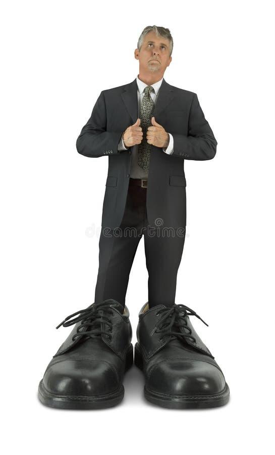 填装人的一些大鞋子站立在巨型发光的企业鞋类 免版税库存图片