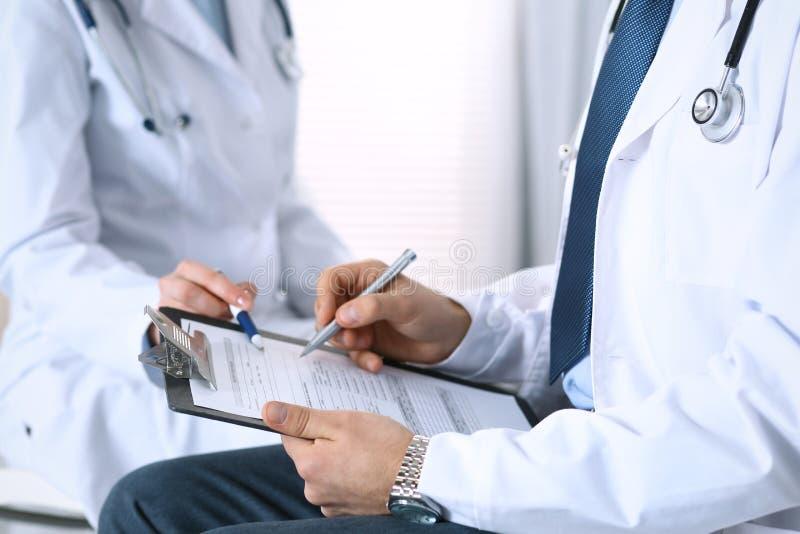 填装在剪贴板,手特写镜头的医疗形式的两位未知的医生 医师问问题对患者或 免版税图库摄影