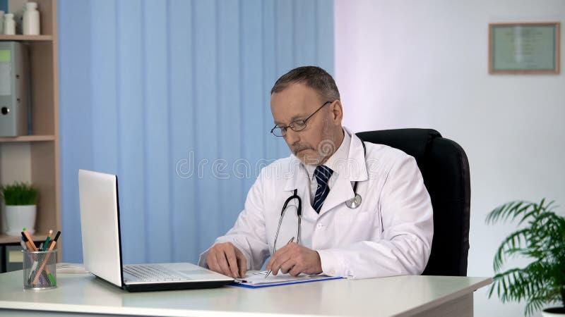 填装在医疗保险的治疗师形成,写处方为患者 免版税库存照片