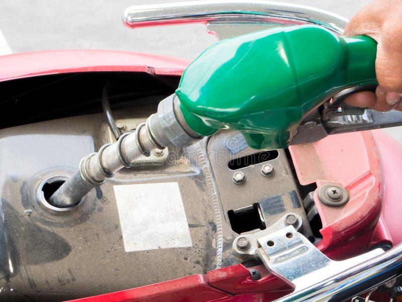 填装在摩托车的燃料在气体/上油驻地 免版税库存照片