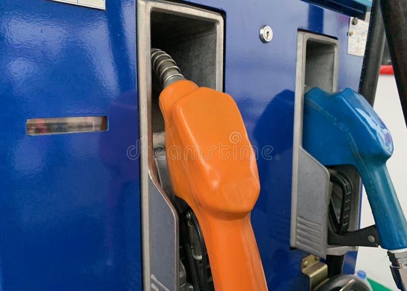 填装在油驻地的油分配器油,橙色和蓝色 库存照片