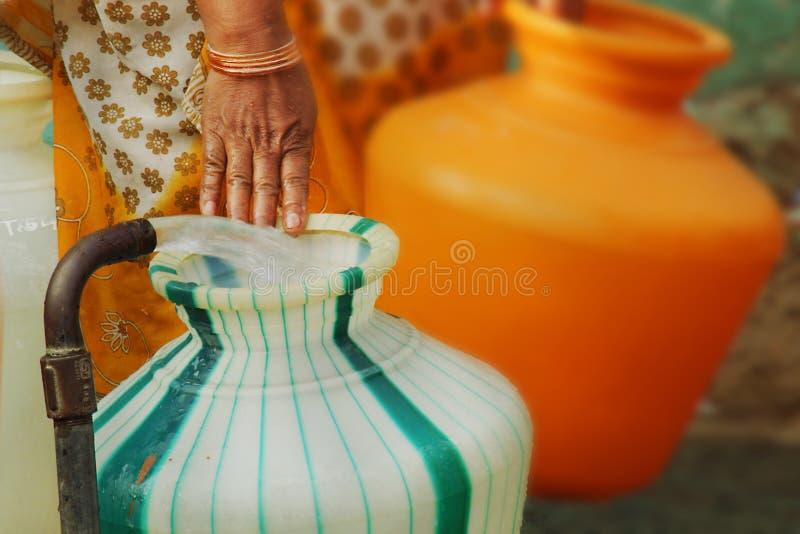 填装塑料水罐的印地安水立场管子 免版税图库摄影