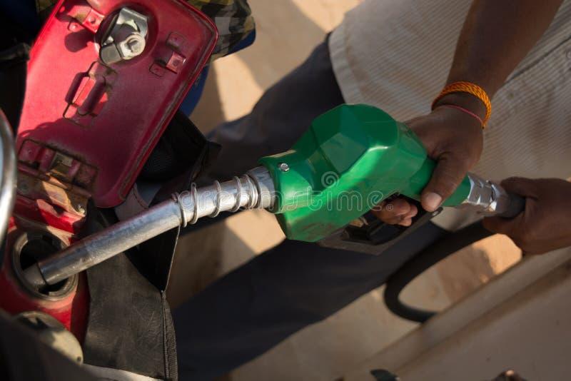 填装汽油的人使用油分配器骑自行车汽油桶关闭  免版税库存照片