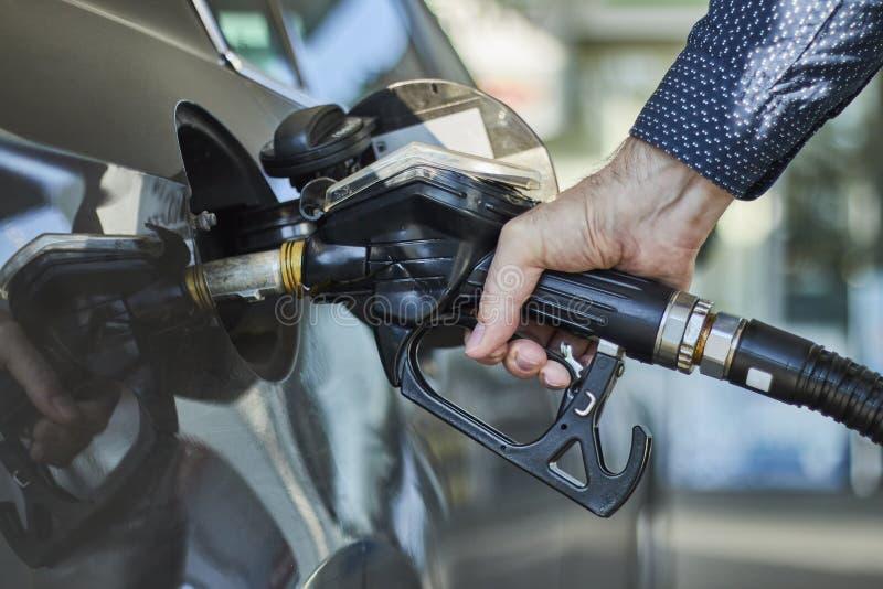 填装汽车的汽油箱的手的特写镜头用在加油站的燃料分配器 免版税库存图片