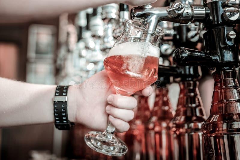 填装玻璃的侍酒者的手用桶装啤酒 免版税图库摄影