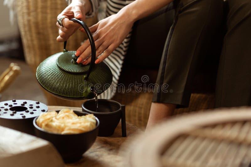 填装黑陶瓷杯子的柔和的平静的夫人用热的茶 免版税图库摄影