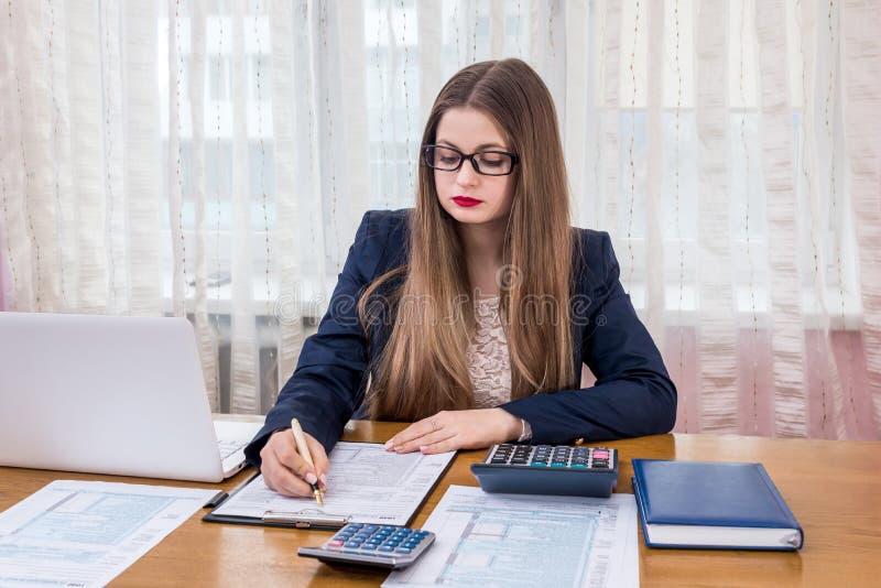 填装1040形式,工作的妇女在办公室 库存照片