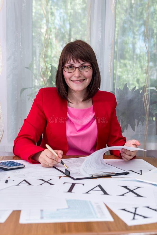 填装1040报税表的微笑的妇女在办公室 免版税库存照片